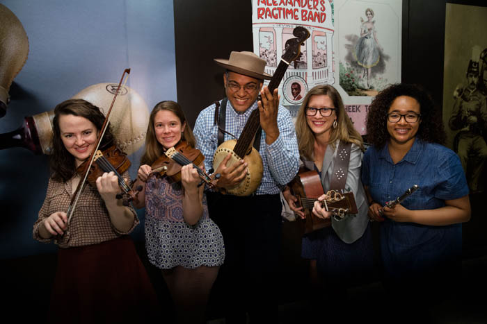 Grammy winning artist Don Flemons stands in the middle of four young women, the Making American Music interns. Each holds a musical instrument.
