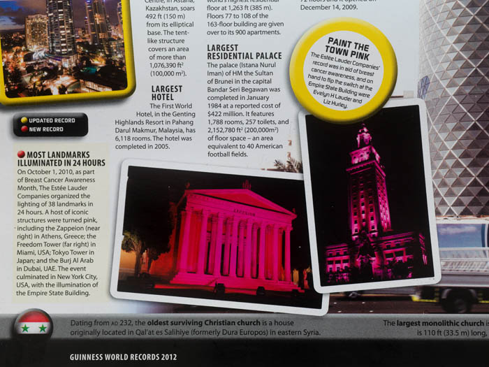 A page of the Guinness Book of World Records, showing landmarks illuminated pink