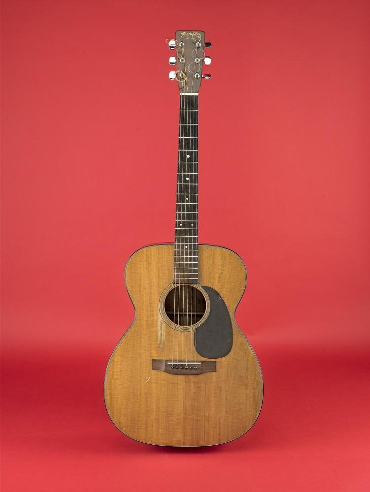 Photo of acoustic guitar on red background