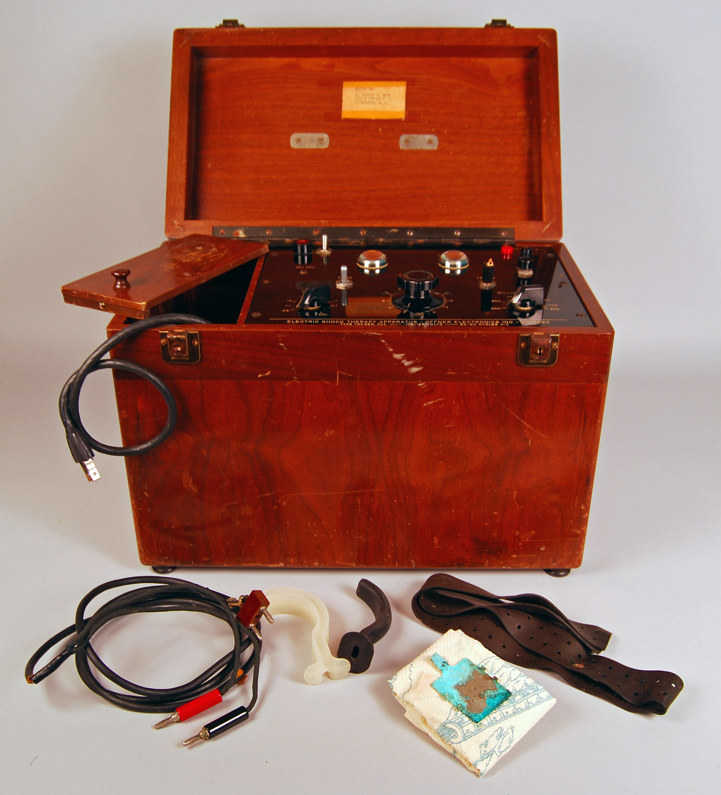 Reddish wooden storage box, quite tall, with lid, which is open. Inside, a control panel with knobs and dials. Outside the box, tubing with electrical-looking plugs, a leather belt, and other items.