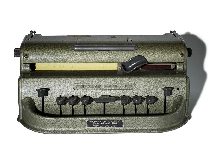 Heavy-looking grey/dark green piece of equipment with six typewriter-style keys.