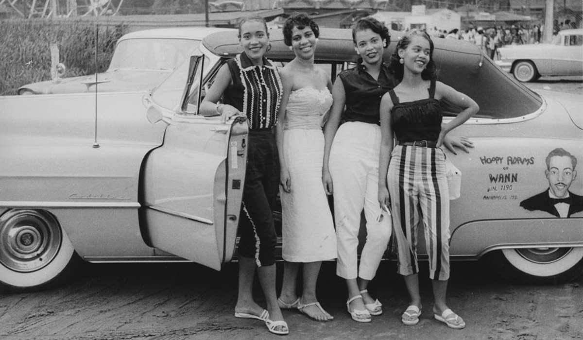 Photograph from the museum's Scurlock Studios collection. Four young women pose in front of a convertible with advertisements for Hoppy Adams of WANN radio station in Annapolis, Maryland.