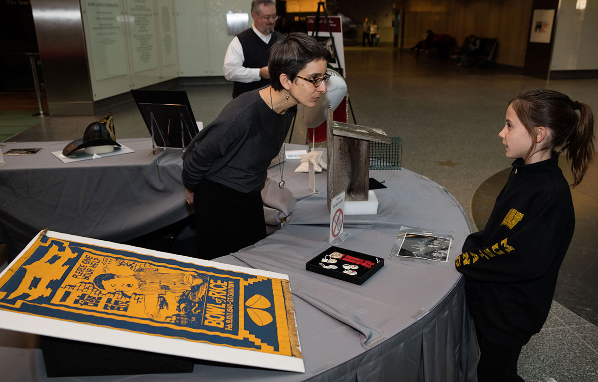 Curator Dr. Amanda B. Moniz speaks with a museum visitor about objects in the collection on Giving Tuesday 2018