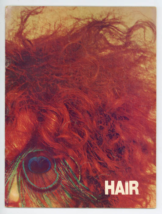 The program for HAIR, showing messy red hair atop someone's head. The person in question has a peacock feather over their eye, masking their identity.