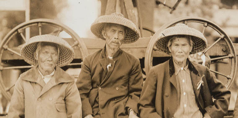 A sepia tone image featuring three men of Chinese descent.