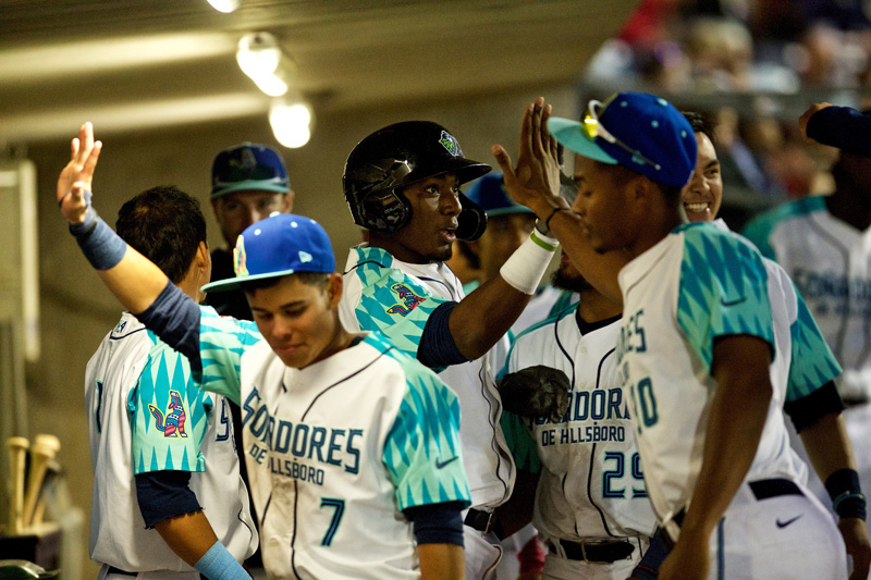 Soñadores players stand and celebrate in a dugout