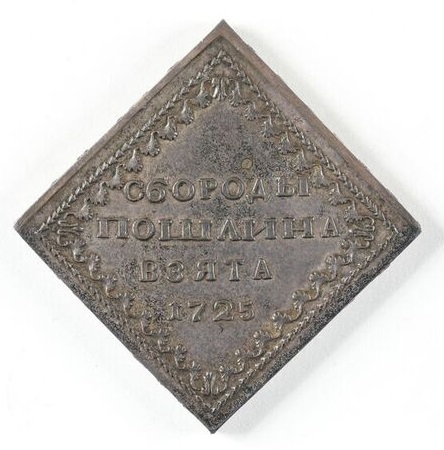 A square piece of silver metal. There is some decoration around the edges and writing in the center.