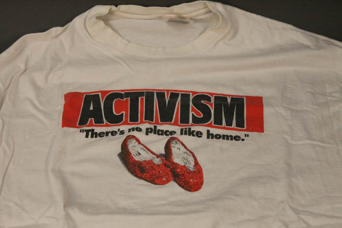 "White T-shirt spread out on table. ""Activism"" in all caps, highlighted in red. ""There's no place like home"" in black with a pair of sequin-covered red shoes."