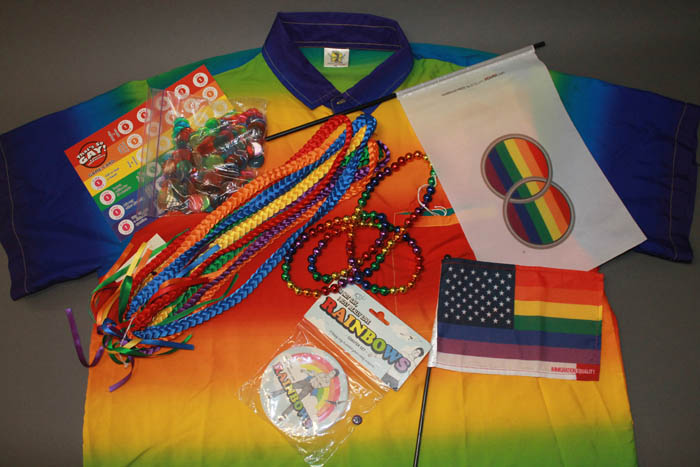 Seven objects in rainbow shades. Collared shirt, decorative buttons/bangles, braided necklace, beaded necklace, flags, and a game card.