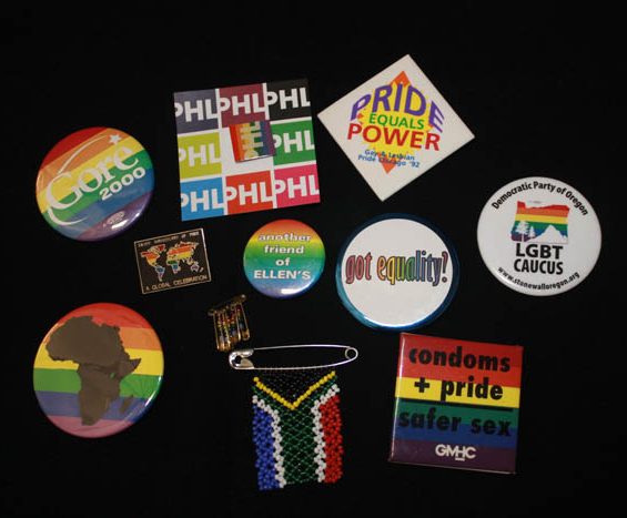 "About 11 buttons with rainbow colors, including ""Gore 2000"" and ""LGBT Caucus."" One shows the continent of Africa in silhouette over rainbow stripes."