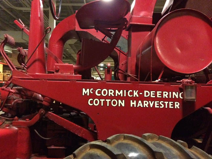 "A detail of the red tractor. It reads ""McCormick-Deering Cotton Harvester"""