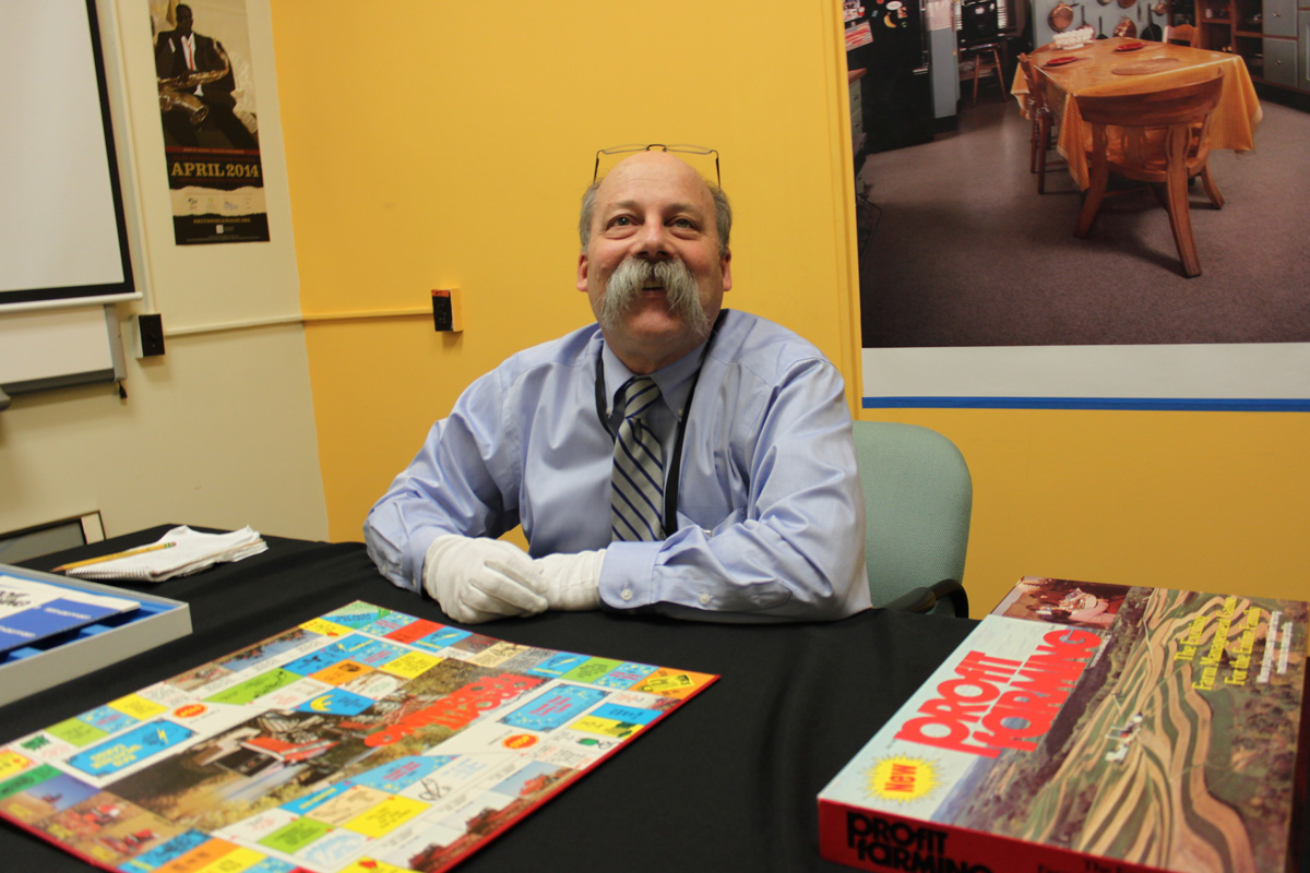 Curator Peter Liebhold poses with the Profit Farming board game's open board..