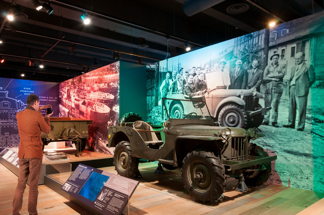 A man looks at a jeep on display.