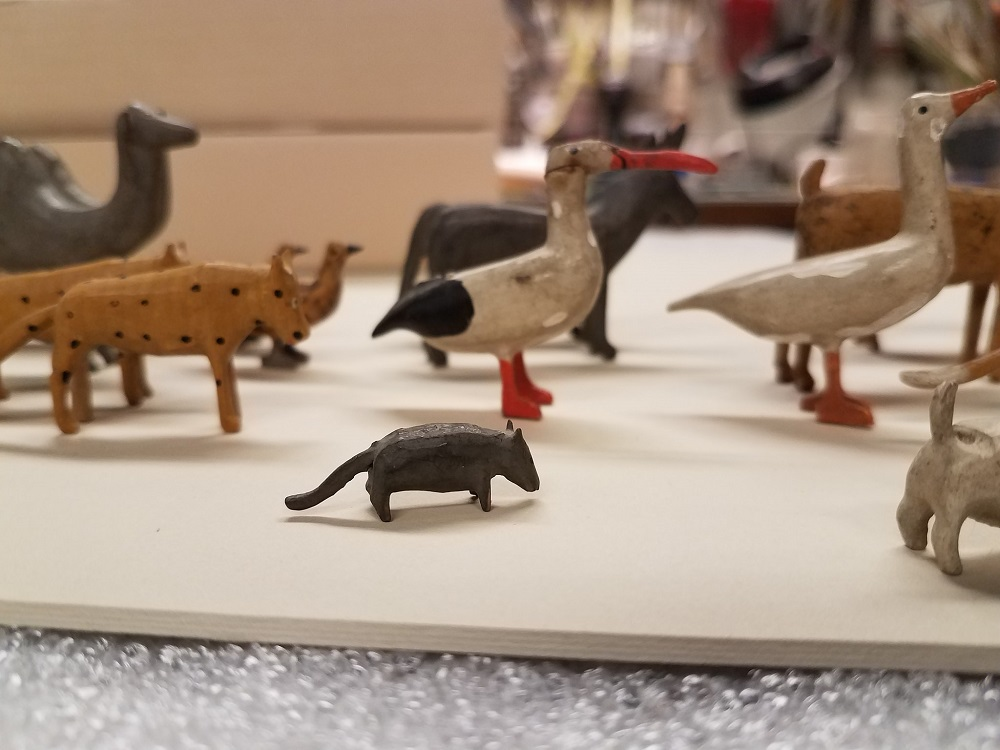 A single carved rat stands among the pairs of birds, camels, and more.