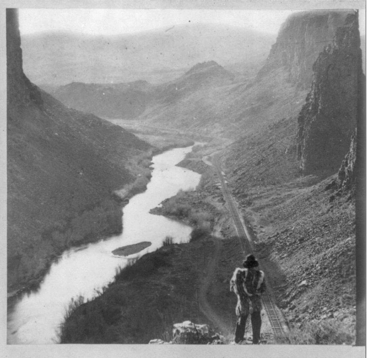 A Native American looks out over a river valley.