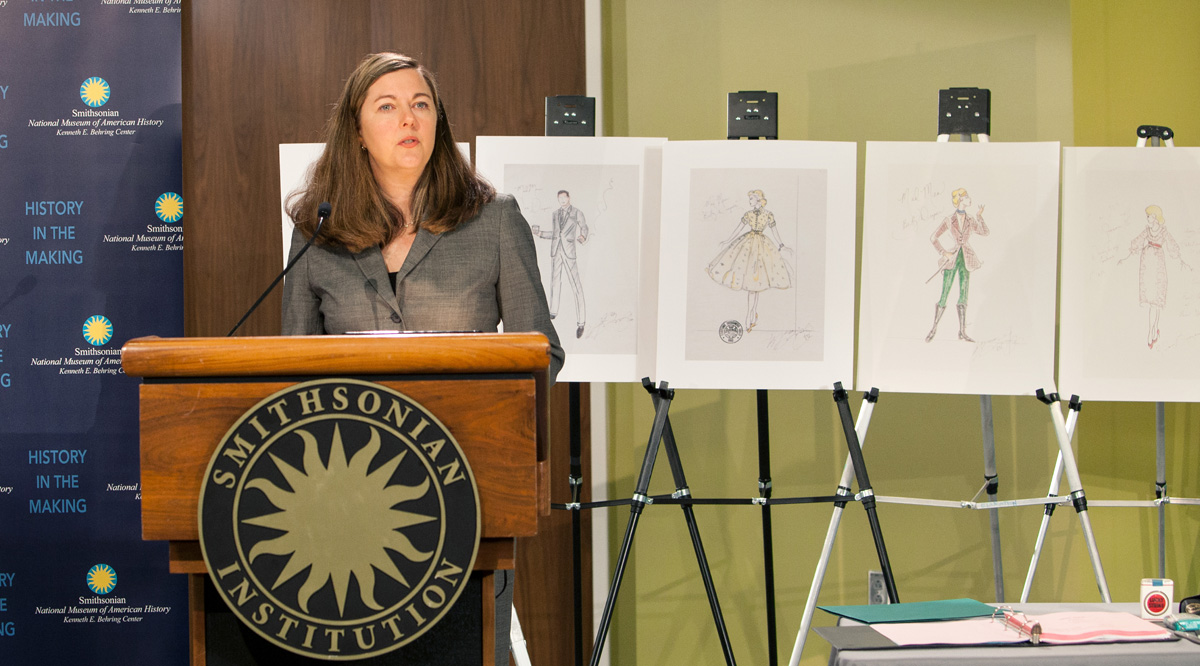 Photograph of curator Kathleen Franz delivering remarks at the Mad Men object donation ceremony. Franz stands at a podium bearing the Smithsonian Institution seal. Behind her are a line of sketches from the television's costume department.