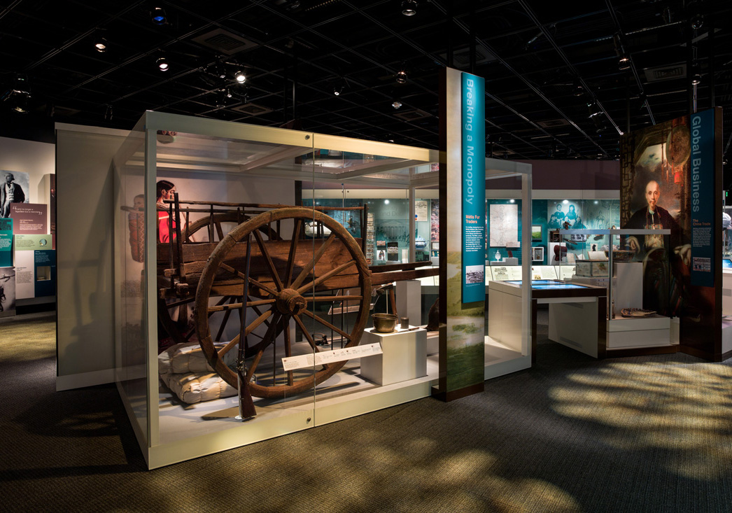 Photograph of the Merchant Era section in the American Enterprise exhibition. In the center of the photo stands a wooden Red River Cart from the 1800s.
