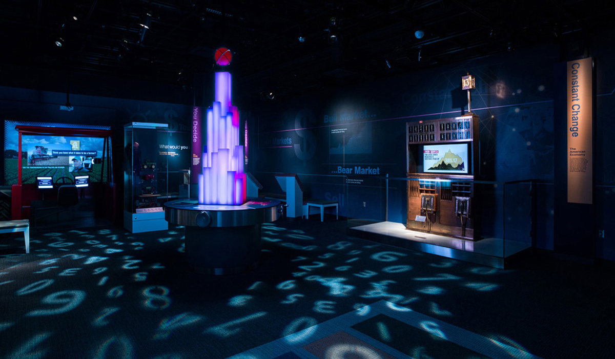 Photograph of the Exchange section in the American Enterprise exhibition. The section is lit dramatically. On the floor, with numbers projected on the floor and a glowing tower in the center.