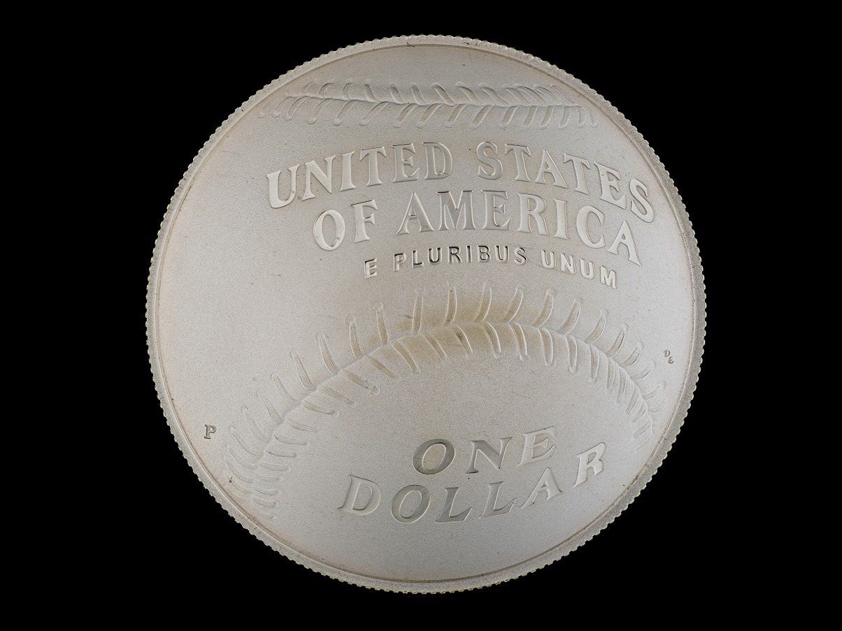 "A round silver coin that has a baseball design and says ""United States of America E Pluribus Unum / One dollar"" on it. Its sides are ridged."