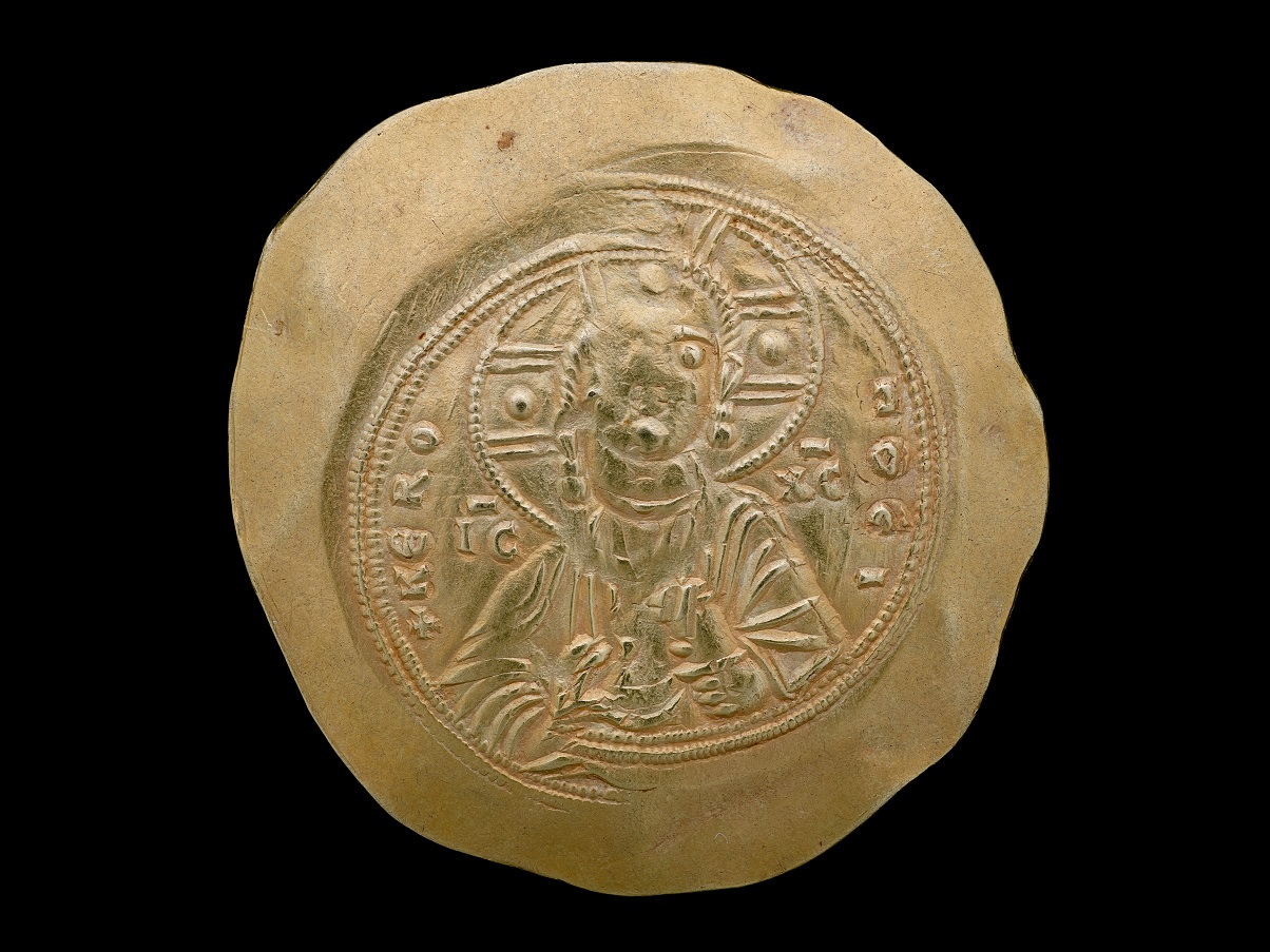 An old, golden coin with a design on it. There appears to be a figure in the center with a crown or halo. Letters or symbols surround it. The edges of the coin appear to be thinner, as if beaten.