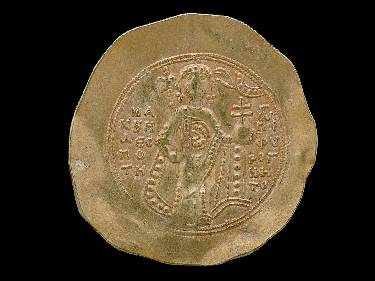 The reverse side of an old, golden coin. There appears to be a crowned, standing figure holding a scepter. There are letters in the spaces surrounding it. The edges are flattened and look to be beaten out to be thinner.