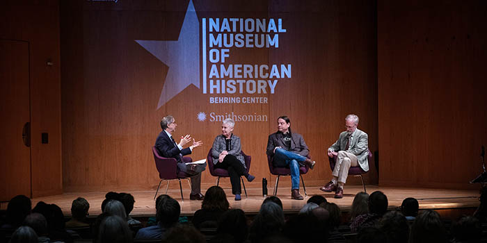 Four people appear in chairs on stage, a panel
