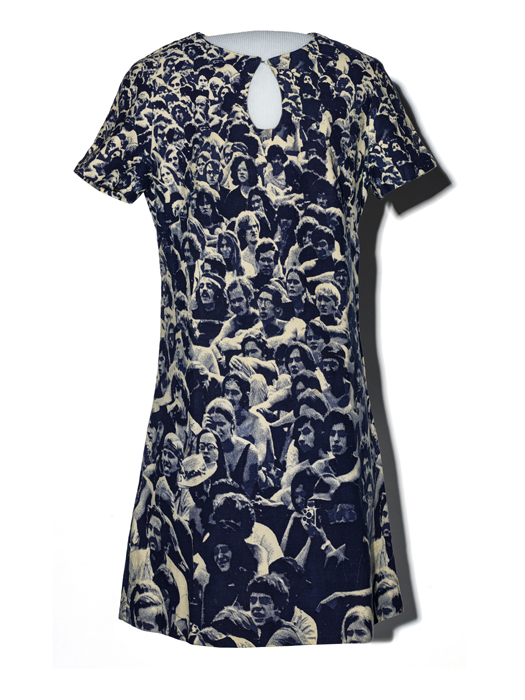 A blue mini-dress with a keyhole detail at the neckline. The fabric features young people sitting in a field.