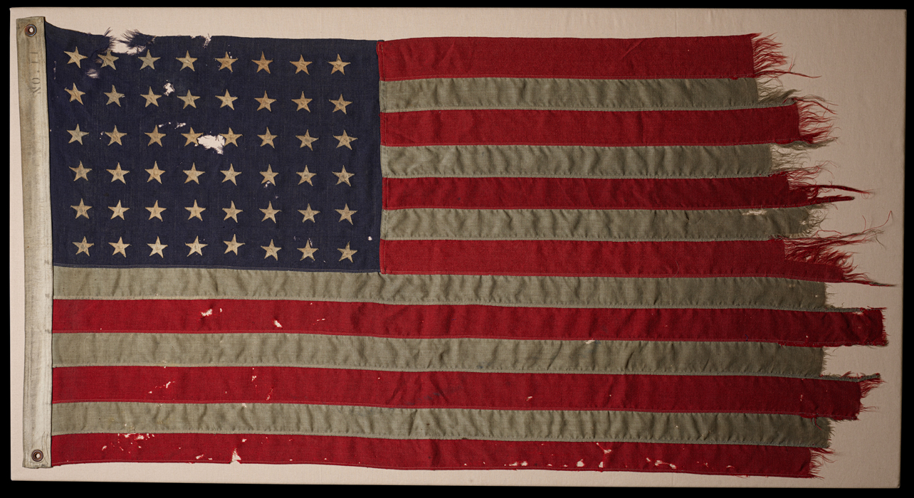 An American Flag, the red and white stripes are literally tattered from use.
