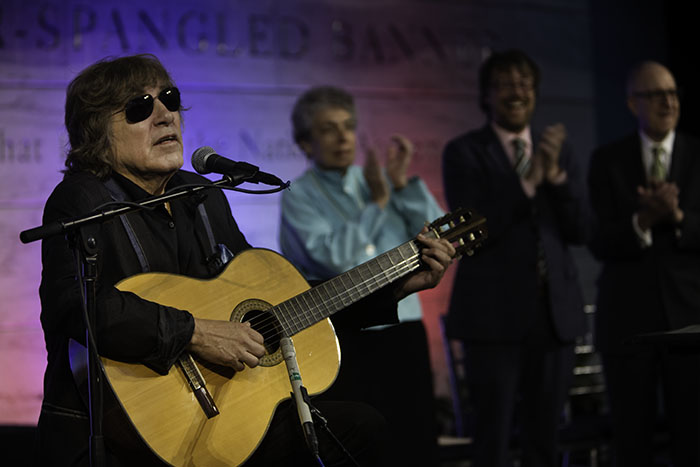 Jose Feliciano, wearing sunglasses and leather jacket, plays acoustic guitar and sings as three others look on.