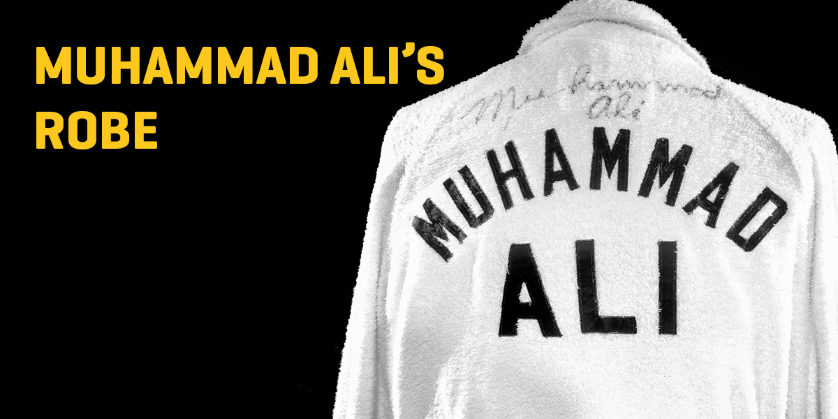 "A photograph of a white terrycloth robe with the words ""Muhammad Ali"" in black text."