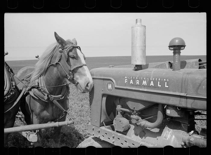 A black and white photo of a horse and a tractor