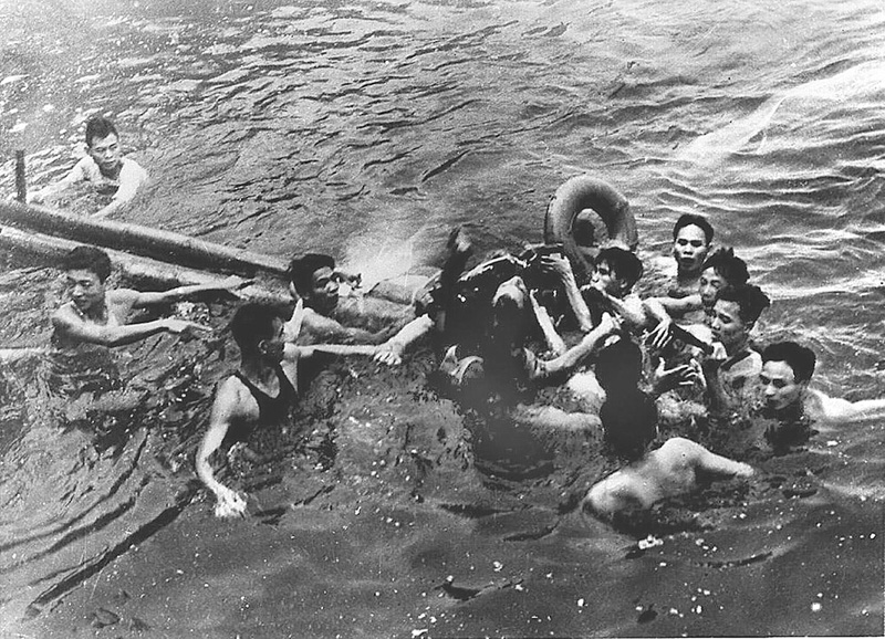Group of men swimming in lake clustered around John McCain