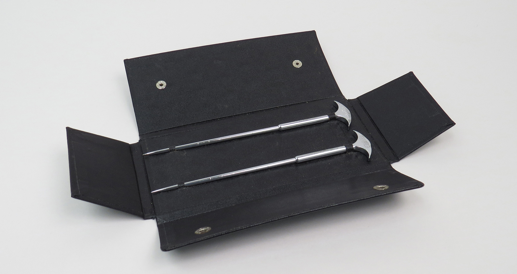 In a black storage case with silver buttons, two silvery metal knives with pointed ends. The non-pointed ends are arch-shaped.