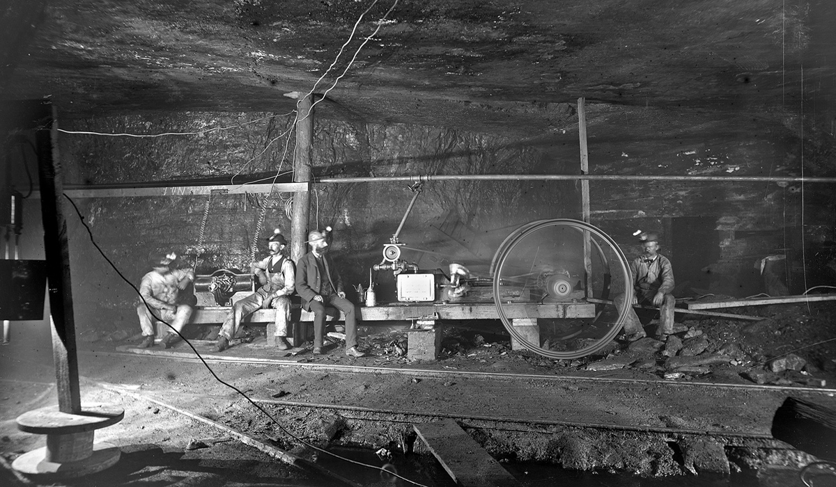 Photograph of four miners resting underground.