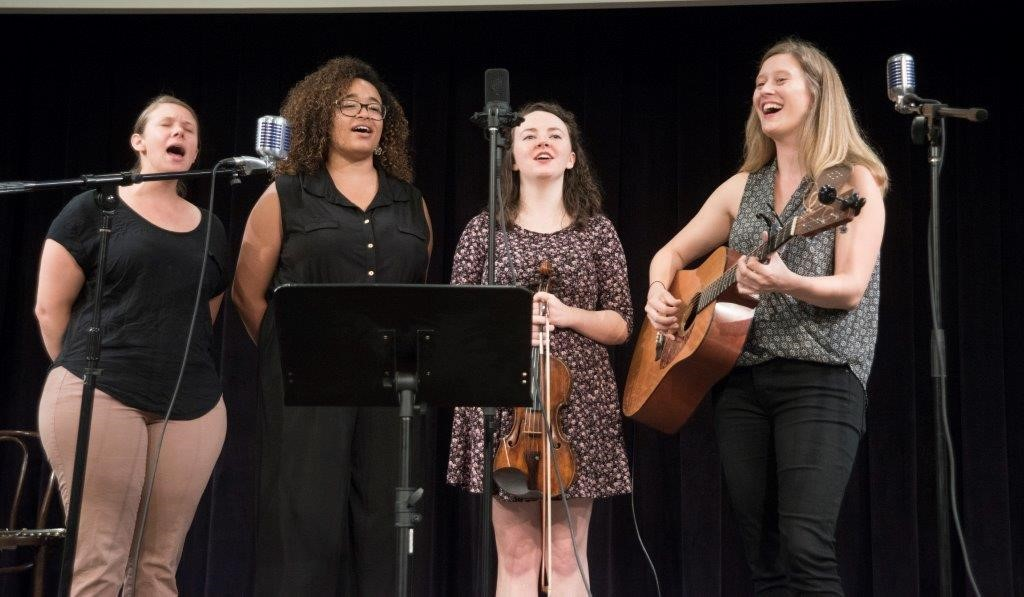Four young women stand on a stage with microphones and a music stand. Background is black. Two hold instruments. Mouths open in song.