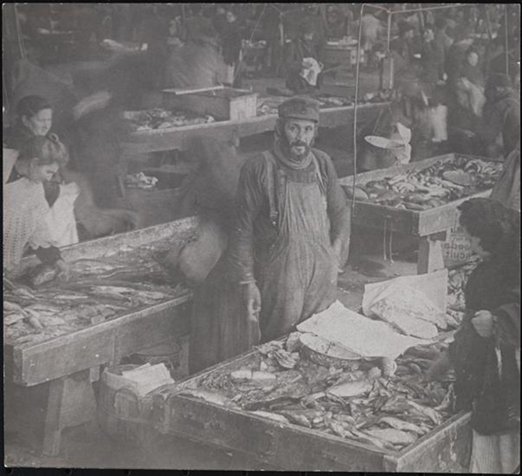 A man in overalls stands among tables piled with seafood