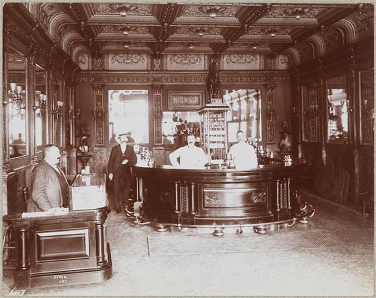 Men pose behind a desk and bar