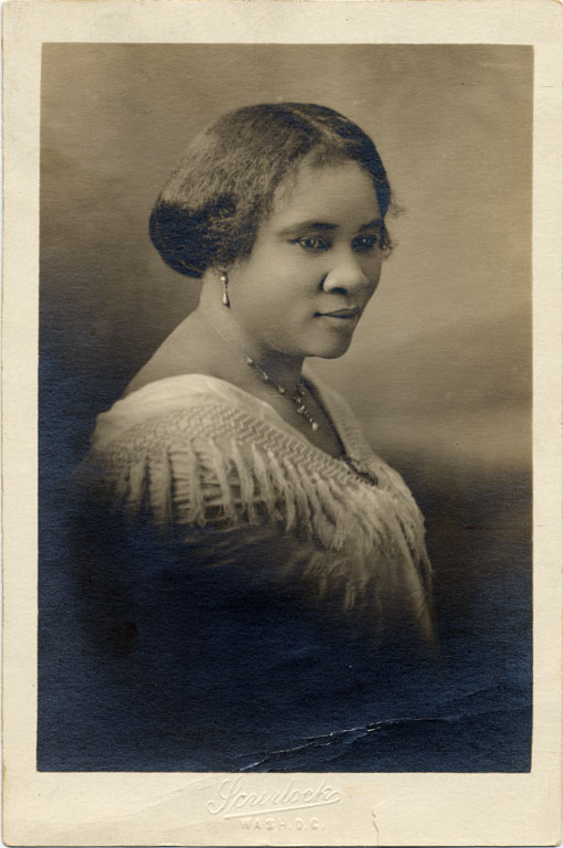 A sepia tone photograph of a woman, with her hair done wearing a necklace. It appears to be the late 19th early 20th century.