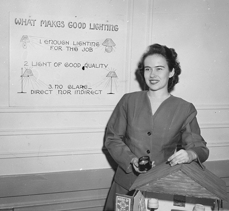 "Black and white photo of a woman with short, curly hair. She smiles at the camera. In her hand, a small candle. She rests her other hand on a model of a house. Behind her, a poster titled ""What Makes Good Lighting."""