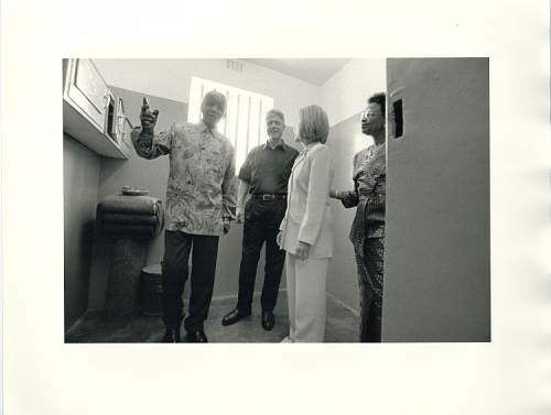 Black and white photo of four people in a small room. Mandela, on left, gestures. President Clinton looks on, a partial smile on his face. Hillary Clinton is seen in profile, standing straight. In the doorway, a woman looks in from the door.