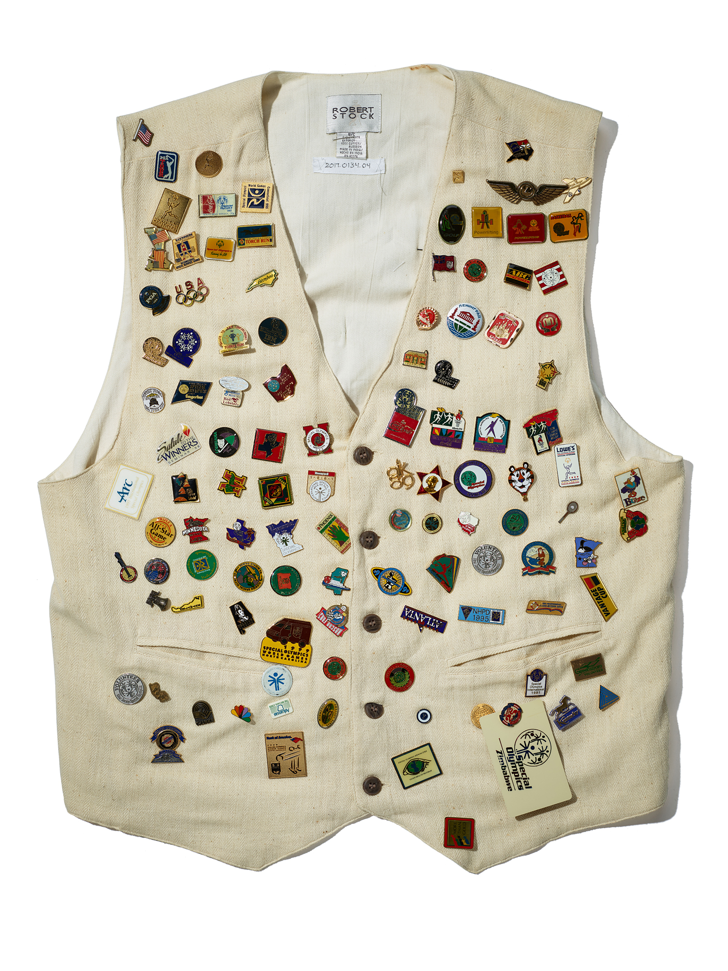 Photo of white vest covered in small, commemorative souvenir pins and buttons. They seem to have different states and countries on them with colorful symbols and text. Probably more than 30.