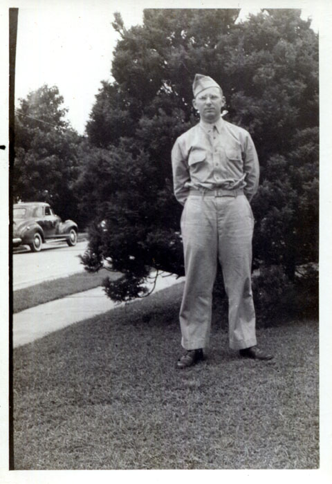 A man in uniform on a lawn.