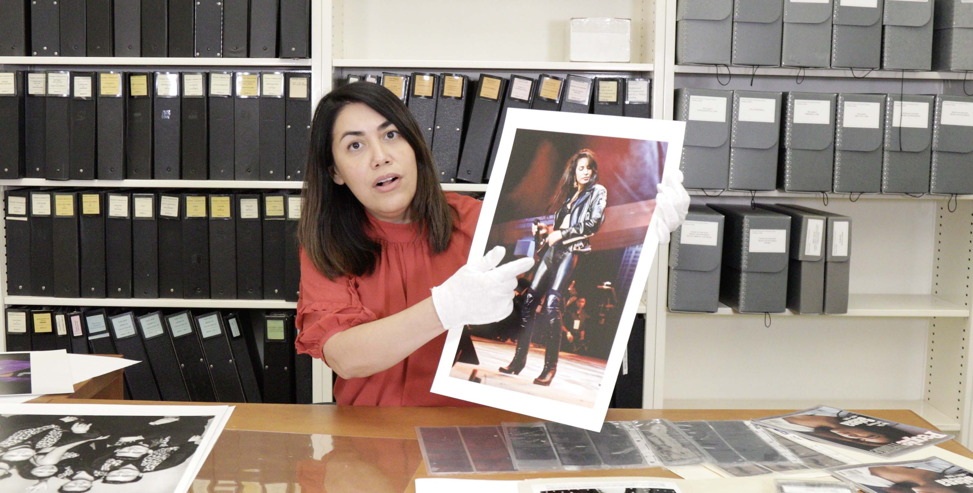 Curator holds photograph of Selena Quintanilla in leather performance outfit