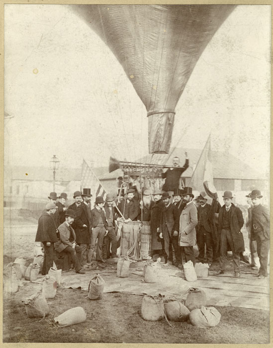 Several men stand in the basket of and around what appears to be a hot air balloon. You can see large horns to project sound from the balloon.