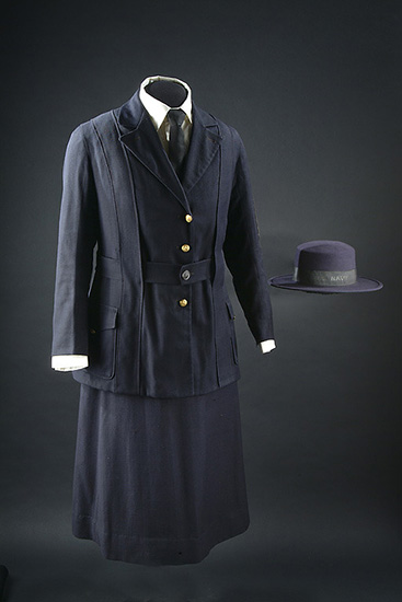 "Blue uniform with collared jacket and skirt. White shirt and tie underneath. Navy blue hat with text ""NAVY"" on ribbon. Four gold buttons."