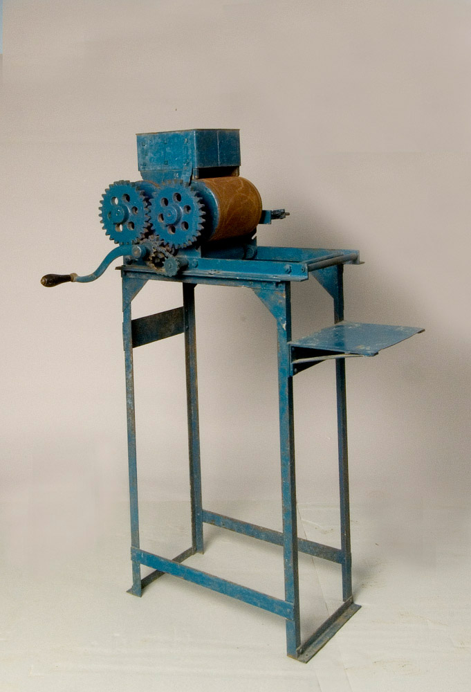 A blue metal machine. You can see two rollers, turned by a hand crank. Ostensibly, you'd put the dough in the top, the rollers would flatten the dough, and a tortilla would drop into the tray to the right.