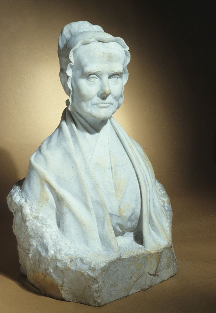 A white marble statue of Mott as an older woman, set against an amber background.