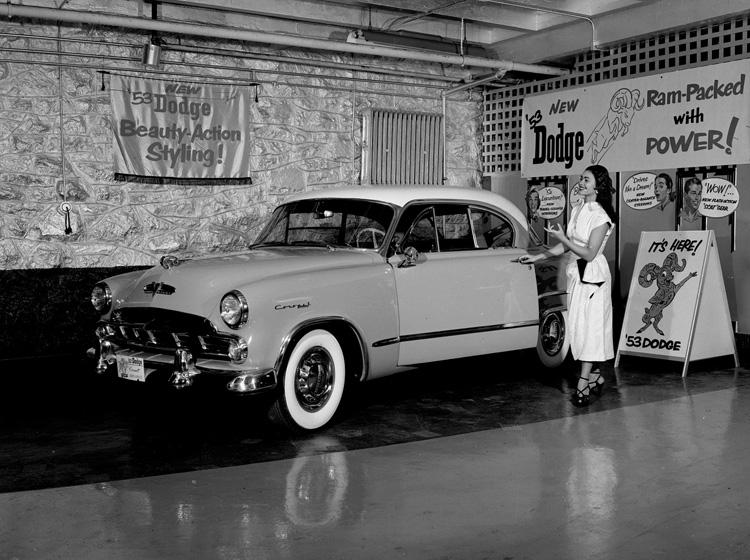 Woman gestures towards car in showroom