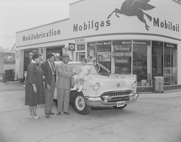 A car salesman and family stand outside a gas station