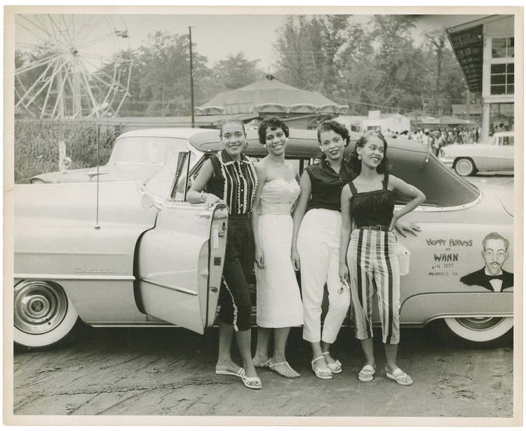 Four women pose in front of a car